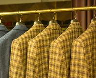 Yellow Checkered Suits on Rack Stock Photo