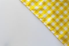 Yellow checkered tablecloth on white background. Yellow picnic tablecloth on white background with copy space stock image