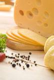 Yellow cheese. With slices, some peppers, parsley and spices. All on wooden table Stock Images