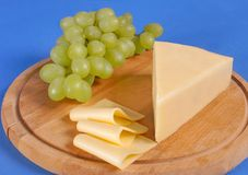 Yellow cheese. A piece of yellow Bulgarian cheese along with several slices and grapes stock photography