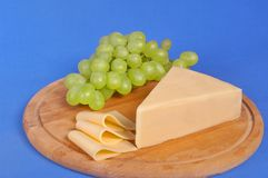 Yellow cheese. A piece of yellow Bulgarian cheese along with several slices and grapes Stock Photo