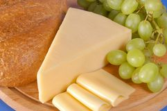 Yellow cheese. A piece of yellow Bulgarian cheese along with several slices, bread and grapes Stock Photos