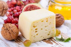 Yellow cheese brick with spices and snacks. On white wooden board Stock Photo