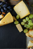 Yellow cheese with grapes on slate background Royalty Free Stock Image
