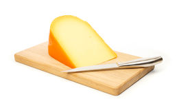 Yellow cheese and kitchen knife on a cutting board. Against white background Stock Photos