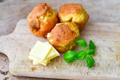 Yellow Cheese and cheese   muffins. Breakfast  from   organic  bio  yellow cheese, home made cheese   muffins  and fresh basil   on a  white wooden background Royalty Free Stock Images