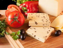 Yellow Cheese with olive on cutting Board stock images