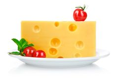 Yellow cheese in plate with tomatoes and leaf Stock Images
