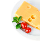 Yellow cheese in plate with tomatoes and leaf Stock Photo