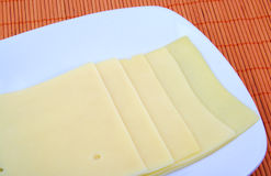 Yellow cheese slices arranged on a white dish. Stock Images