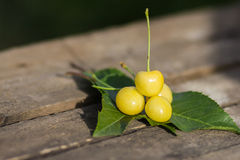 Yellow cherries on a wooden table Royalty Free Stock Photos