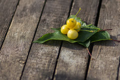 Yellow cherries on a wooden table Stock Images
