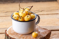 Yellow cherry in a rustic style on a wooden background. Berries of ripe fresh cherries in a cup. Royalty Free Stock Image