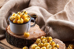Yellow cherry in a rustic style on a wooden background. Berries of ripe fresh cherries in a cup. Stock Photos