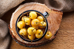 Yellow cherry in a rustic style on a wooden background. Berries of ripe fresh cherries in a cup. Stock Photography