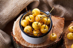 Yellow cherry in a rustic style on a wooden background. Berries of ripe fresh cherries in a cup. Royalty Free Stock Photo