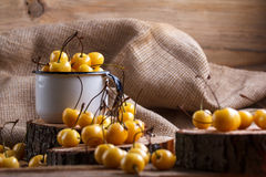 Yellow cherry in a rustic style on a wooden background. Berries of ripe fresh cherries in a cup. Stock Image