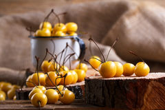 Yellow cherry in a rustic style on a wooden background. Berries of ripe fresh cherries in a cup. Royalty Free Stock Images