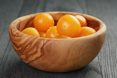 Yellow cherry tomatoes in olive bowl on wood table Royalty Free Stock Photos