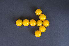 Yellow cherry tomatoes in a shape of an arrow on dark background Royalty Free Stock Photography