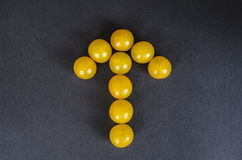 Yellow cherry tomatoes in a shape of an arrow on dark background Royalty Free Stock Images