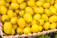 Yellow cherry tomatoes in wicker basket Royalty Free Stock Photography