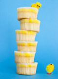 Yellow chick and a cupcake tower. Yellow chick looking at a huge tower made of lemon cupcakes and his friend sitting on the top stock photos