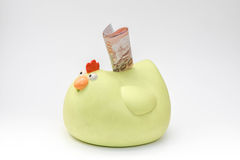 Yellow chicken piggy bank and money inserting stock image