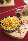 Yellow chickpeas lie in an oriental plate on a wooden spice board royalty free stock photo