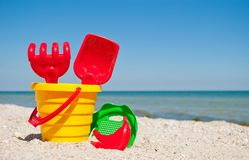 Yellow child pail with a red handle, plastic red spatula and rake, and a plastic green sieve, a red sand form in the form of a ban Royalty Free Stock Photo