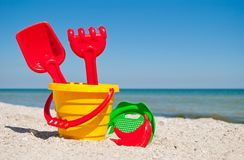 Yellow child pail with a red handle, plastic red spatula and rake, and a plastic green sieve, a red sand form in the form of a ban Stock Photo