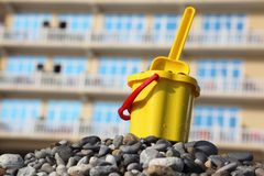 Yellow children's bucket with scoop on pebble Royalty Free Stock Photography