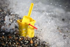 Yellow children's bucket with scoop on seacoast Royalty Free Stock Images