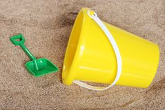Yellow childs pail in the sand Stock Images