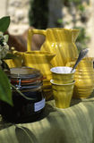 Yellow china jugs and cups,jar of jam outdoors Royalty Free Stock Photography