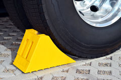 Yellow chock at the wheel of a parked truck Stock Image