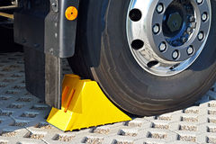 Yellow chock at the wheel of a parked truck Royalty Free Stock Photo