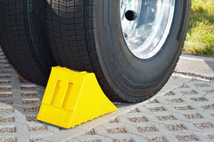Yellow chock at the wheel of a parked truck Royalty Free Stock Image
