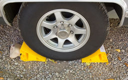 Yellow chock at the wheel. Yellow wheel chock or wheel stopper Royalty Free Stock Photography