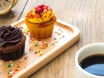 Yellow and chocolate cupcakes put on a spherical wooden plate. Beside of cupcake have Cactus and white coffee mug. All of it rests on wooden table Royalty Free Stock Photo