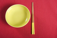 Yellow chopsticks and bowl on red table place setting mat. Royalty Free Stock Images