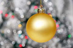 Yellow christmas ball against distant lights. Yellow christmas ball against silvery background and distant lights Royalty Free Stock Images