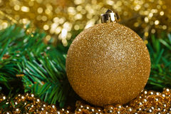 Yellow christmas ball with green fir-tree branch Royalty Free Stock Images