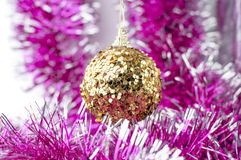 Yellow christmas ball on purple decoration Royalty Free Stock Images