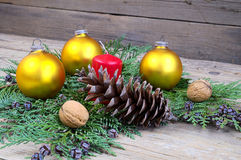 Yellow Christmas balls with red candle with cone and walnuts on wooden table Stock Photo