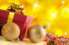 Yellow Christmas decoration with two balls and gift Diagonal com Stock Images