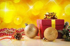 Yellow Christmas decoration with two balls and gift Stock Photos