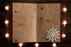Yellow Christmas lights with a blank book on wooden background. Christmas background Stock Photos