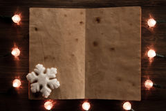 Yellow Christmas lights with a blank book on wooden background. Christmas background Stock Image