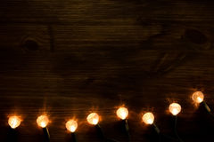 Yellow Christmas lights on wooden background. Royalty Free Stock Photography